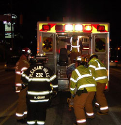 EMTs load a patient into their ambulance.